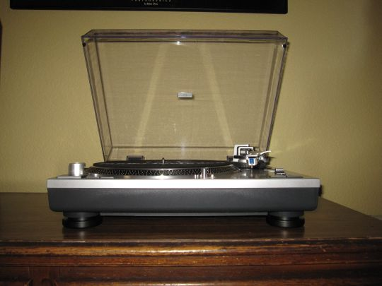 Photo shows the Audio-Technica AT-LP120-USB from the front. The platter and controls emerge from the eye-level platform.
