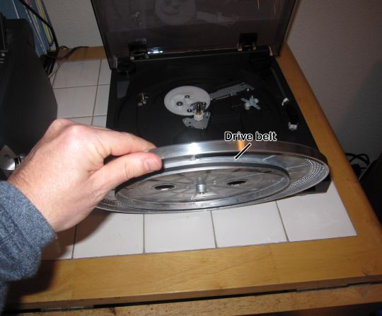 Photo shows a hand holding up a platter with a rubber drive belt wrapped around the bottom. The unassembled Audio-Technica AT-LP2D-USB turntable is in the background.