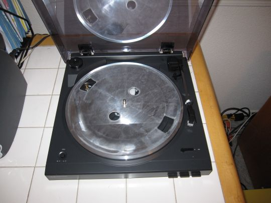 Photo shows a nearly-assembled Audio-Technica AT-LP2D-USB turntable. Prominent is a bare metal platter with four holes. The pulley that spins the platter is visible through one hole. The drive belt is over the pulley.
