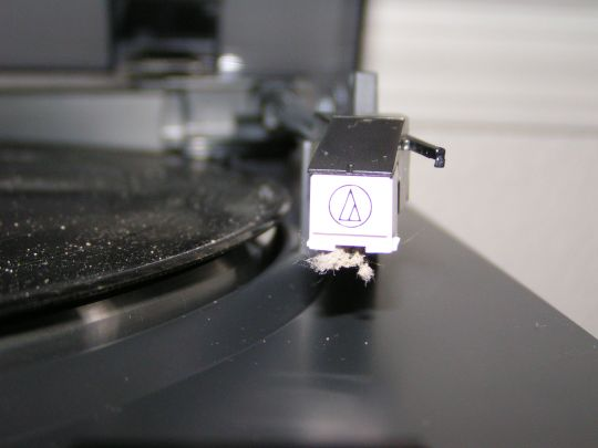 Close-up photo shows the Audio-Technica AT-3600L cartridge. The stylus is covered in dust. Dust is also visible on the LP sitting on the adjacent turntale platter.