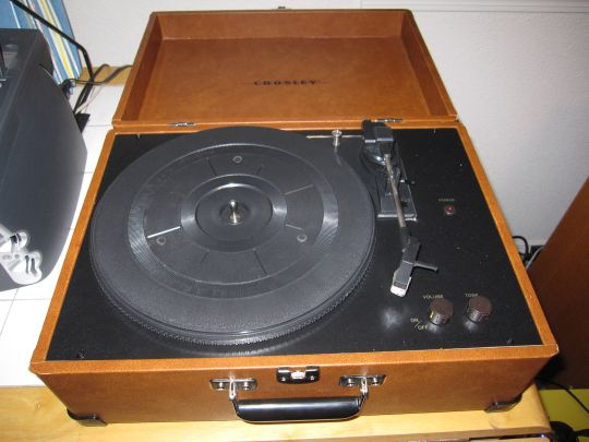 Photo shows the Crosley CR249 turntable on a table from above. The cover is open, revealing the platter and controls.