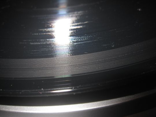 Close-up photo shows a black record with a gray ring starting from the outer edge and continuing through the first track. Damage was from a defective stylus on a Grace Digital Audio Vinylwriter (AVPUSB01S) USB turntable.