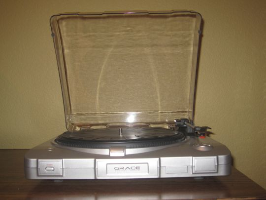 Photo shows the front side of the Grace Digital Audio Vinylwriter (AVPUSB01S) USB turntable. The dustcover is up.