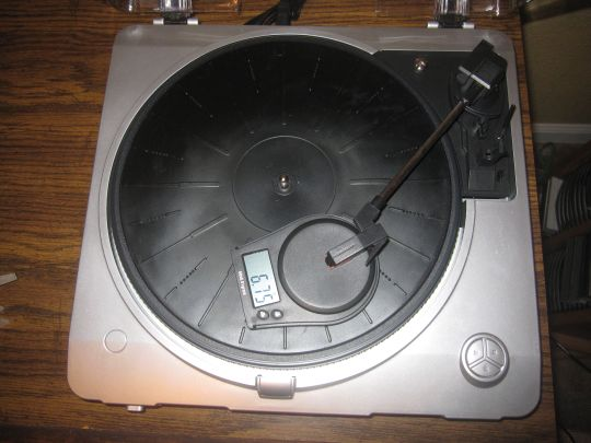 Photo shows the stylus of the Grace Digital Audio Vinylwriter (AVPUSB01S) USB turntable on a tracking force scale. The digital readout shows 6.75 grams/