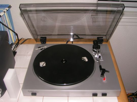 Photo shows a view of the Ion Audio TTUSB05  turntable from above. The cartridge/needle assembly is detached from the tonearm and resting on the body of the record player.