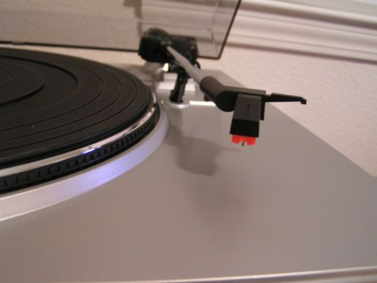 Close-up photo of the cartridge and stylus on the Ion Audio TTUSB05 turntable. Platter with mat is partially visible on left side of photo.